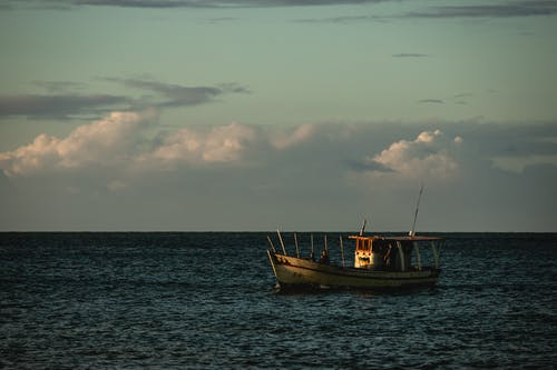 White and Blue Boat on Sea Under White Clouds