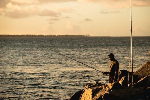 Man in Black Shirt Fishing on Sea