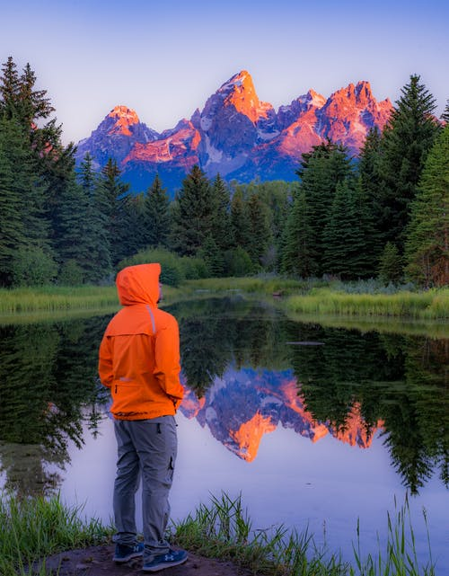 Man in Orange Hoodie Standing on Green Grass Field Near Lake
