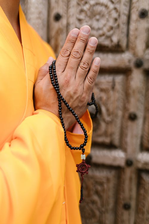 Person in Yellow Long Sleeves Holding Black Beads