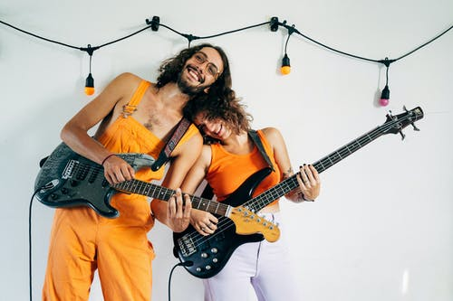 A Happy Couple Playing Electric Guitars