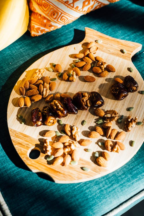 Close-Up Shot of Assorted Nuts on a Wooden Tray