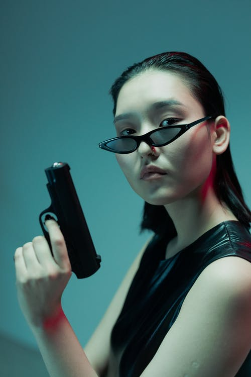 Woman in Black Tank Top Wearing Black Framed Eyeglasses Holding Black Smartphone