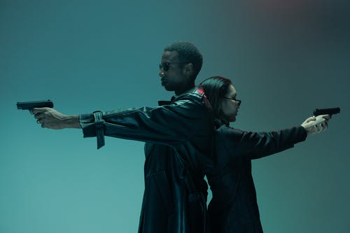 Man in Black Leather Jacket Standing Beside Woman in Black Coat