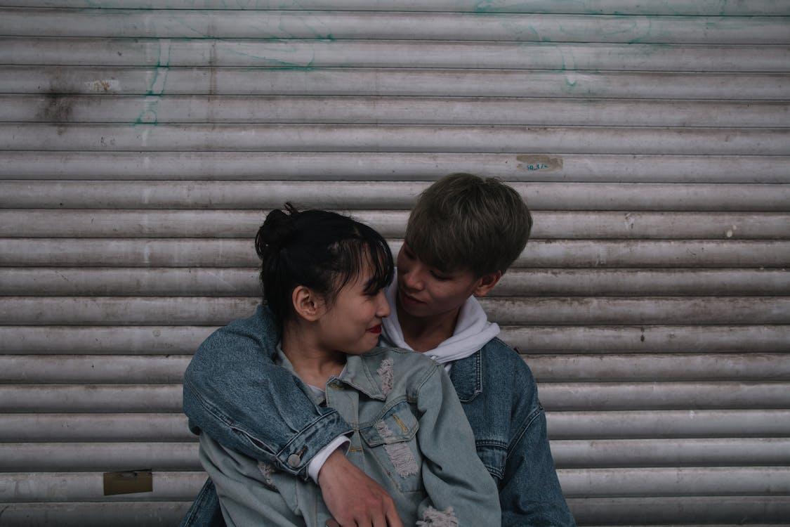 Boy Wearing Blue Denim Jacket and Embrace Woman Wearing Jacket
