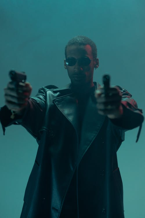 Man in Black Leather Jacket Holding Guns