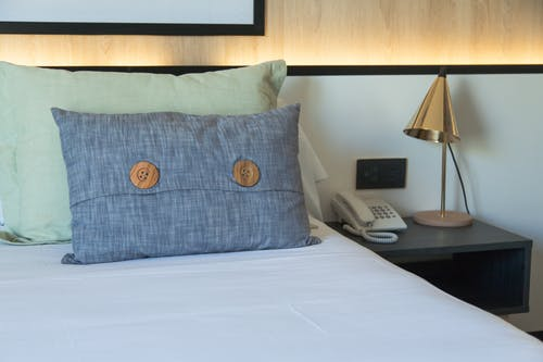 Blue and White Throw Pillows on White Bed