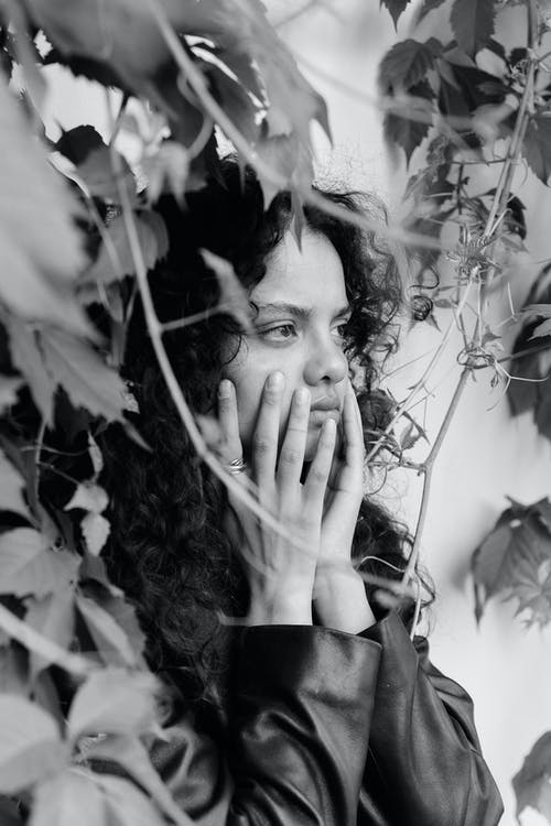 Grayscale Photo of a Woman Touching Her Face Near Vines