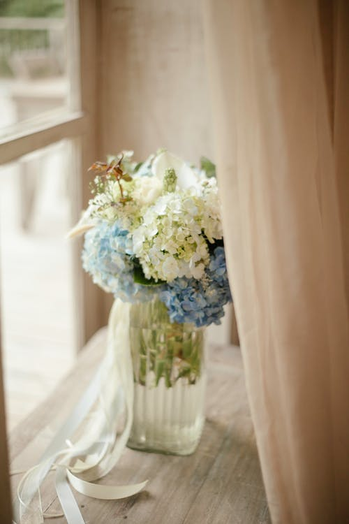 White and Blue Flower Bouquet in Glass Vase Decorated with Ribbons