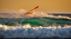 Person Ridding Wind Boat Above Ocean Wave