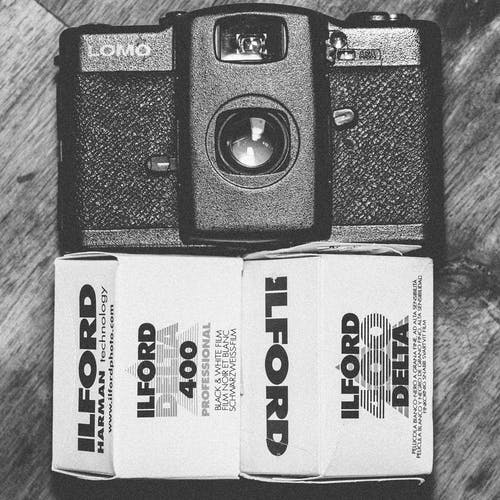 Black Lomo Compact Camera Beside Ilford Delta 400 Black & White Film Box