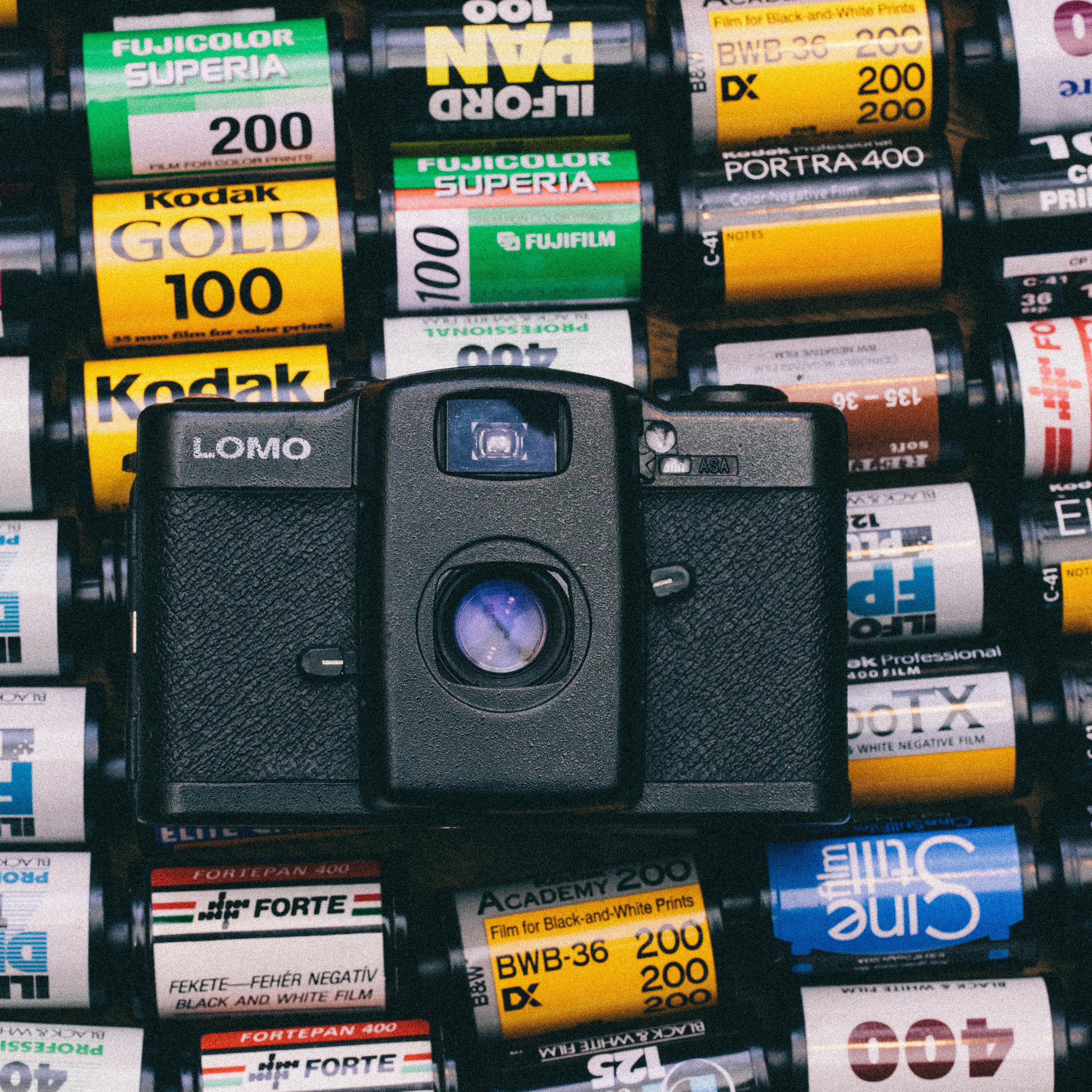 black lomo camera on top of photo films lot