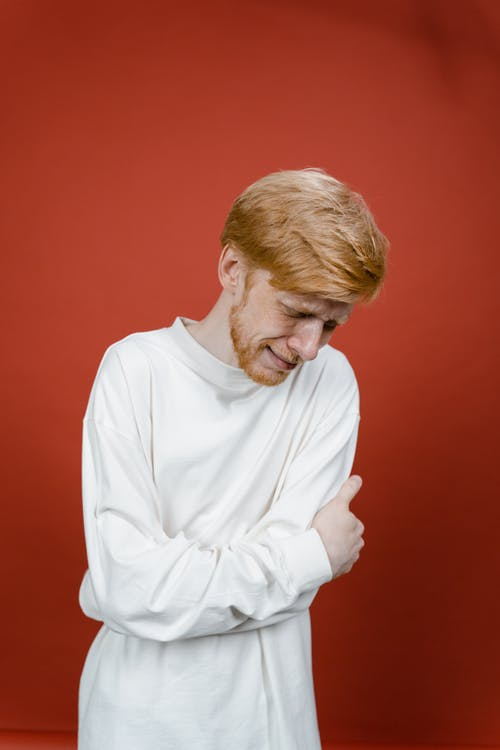 Man in White Long Sleeve Shirt Standing Near Red Wall and Crying
