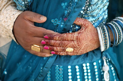 Woman's Hands with Henna Tattoos on Blue and White Dress