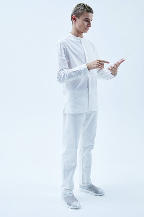 Man in White Suit Holding a Piece of Glass