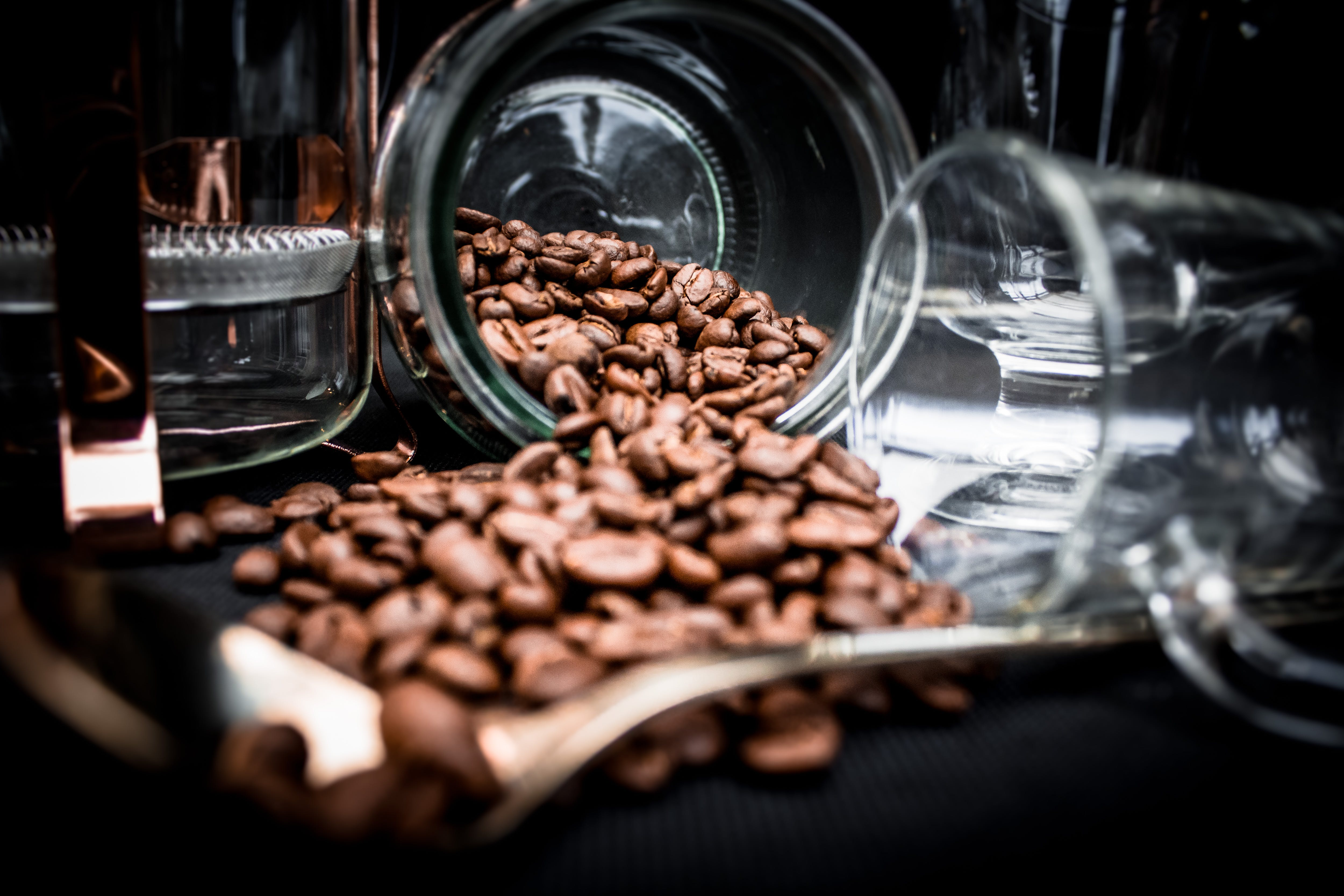 Coffee Beans Spoiling on Clear Glass Jar Near Clear Glass Mug