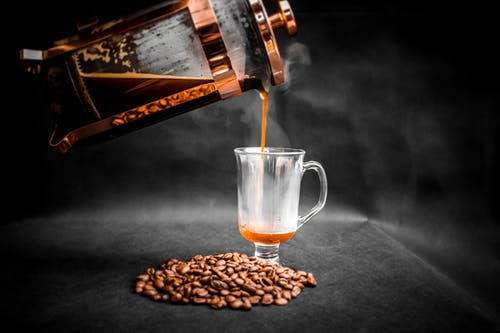 Aromatic hot coffee being poured from French press into elegant glass with pile of coffee beans beside on black background