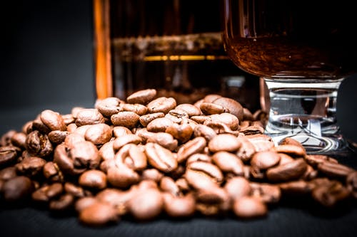 Coffee beans with glass and French press on black background