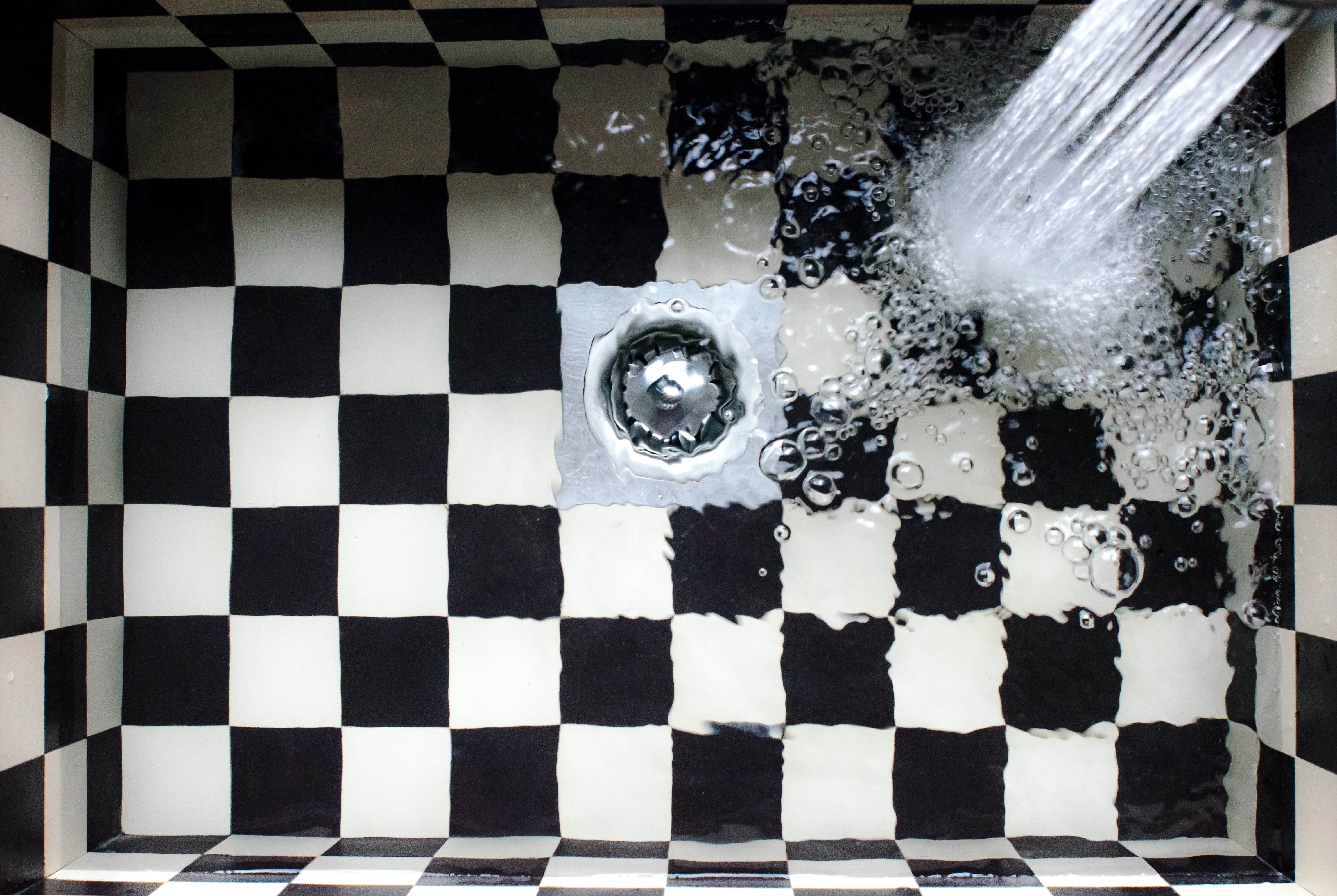 Water Flowing on White and Black Checked Bath Tub