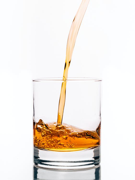 Clear Drinking Glass Filled With Brown Liquid