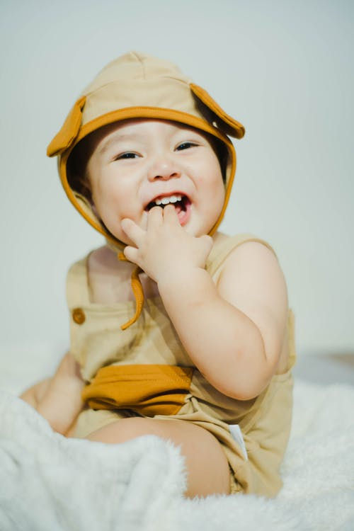 Close-Up Photo of a Cute Kid with His Fingers in His Mouth