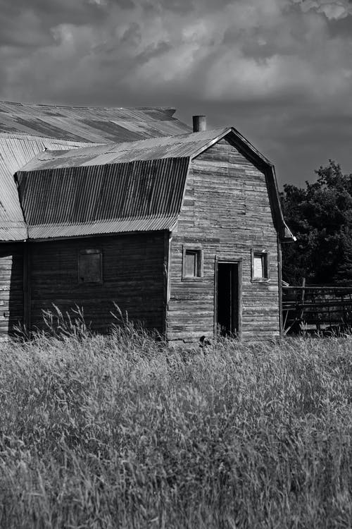 Grayscale Photo of a Barn Under a Cloudy Sky