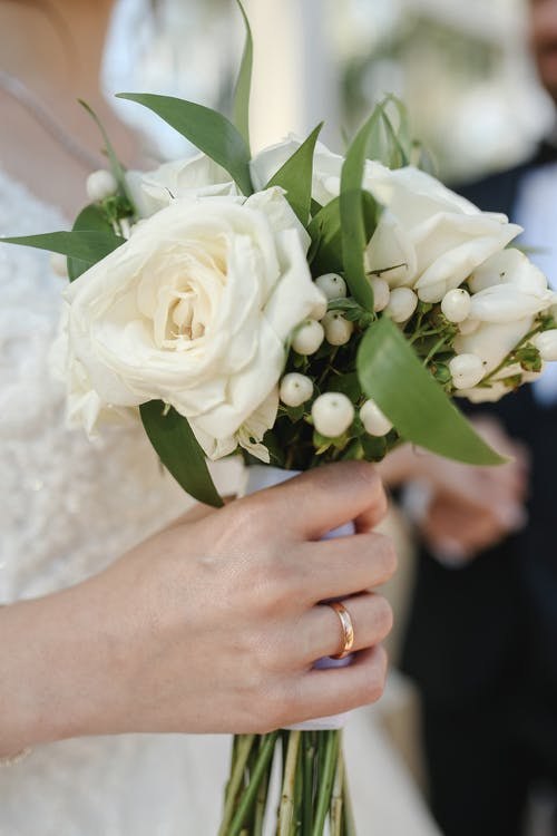 Woman Wearing Gold Wedding Ring Holding a White Bouquet of Flowers