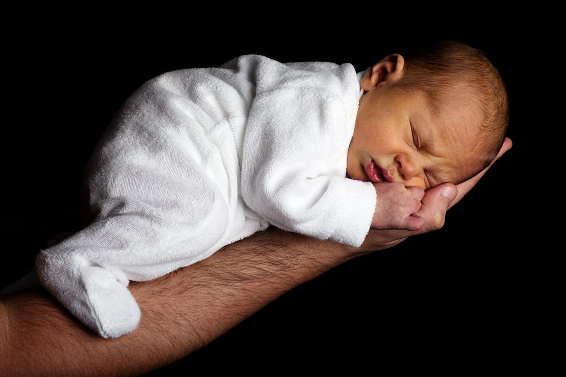 Baby in White Onesie Sleeping on Person's Hand