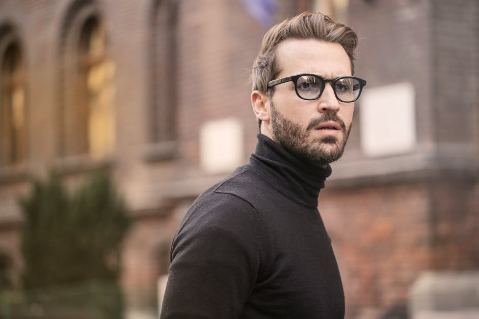 Man Standing Near Building White Black Turtleneck Shirt
