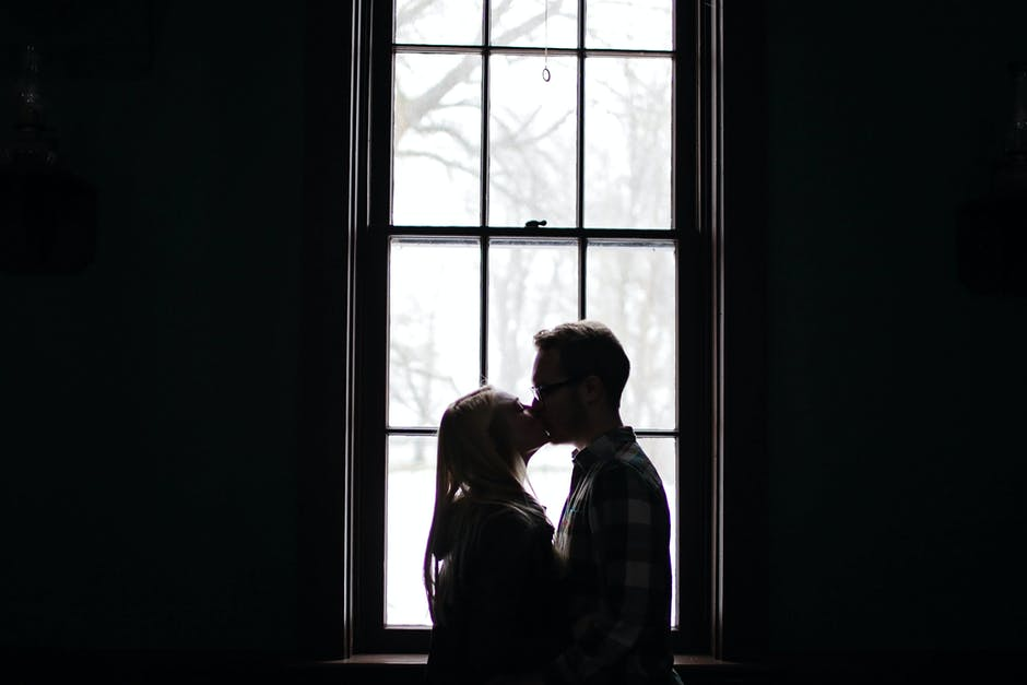 Man and Woman Kissing Beside Window