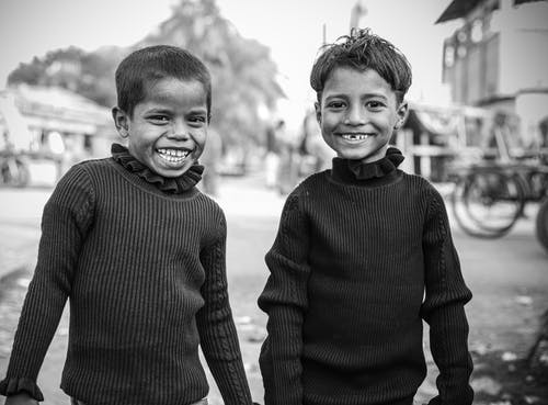 Grayscale Photo of Two Boys in Long Sleeves Smiling
