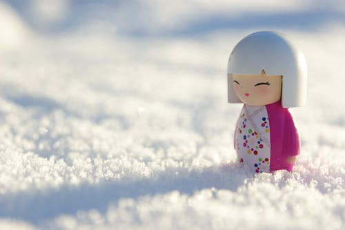 White Snowman With Pink Scarf on Snow Covered Ground