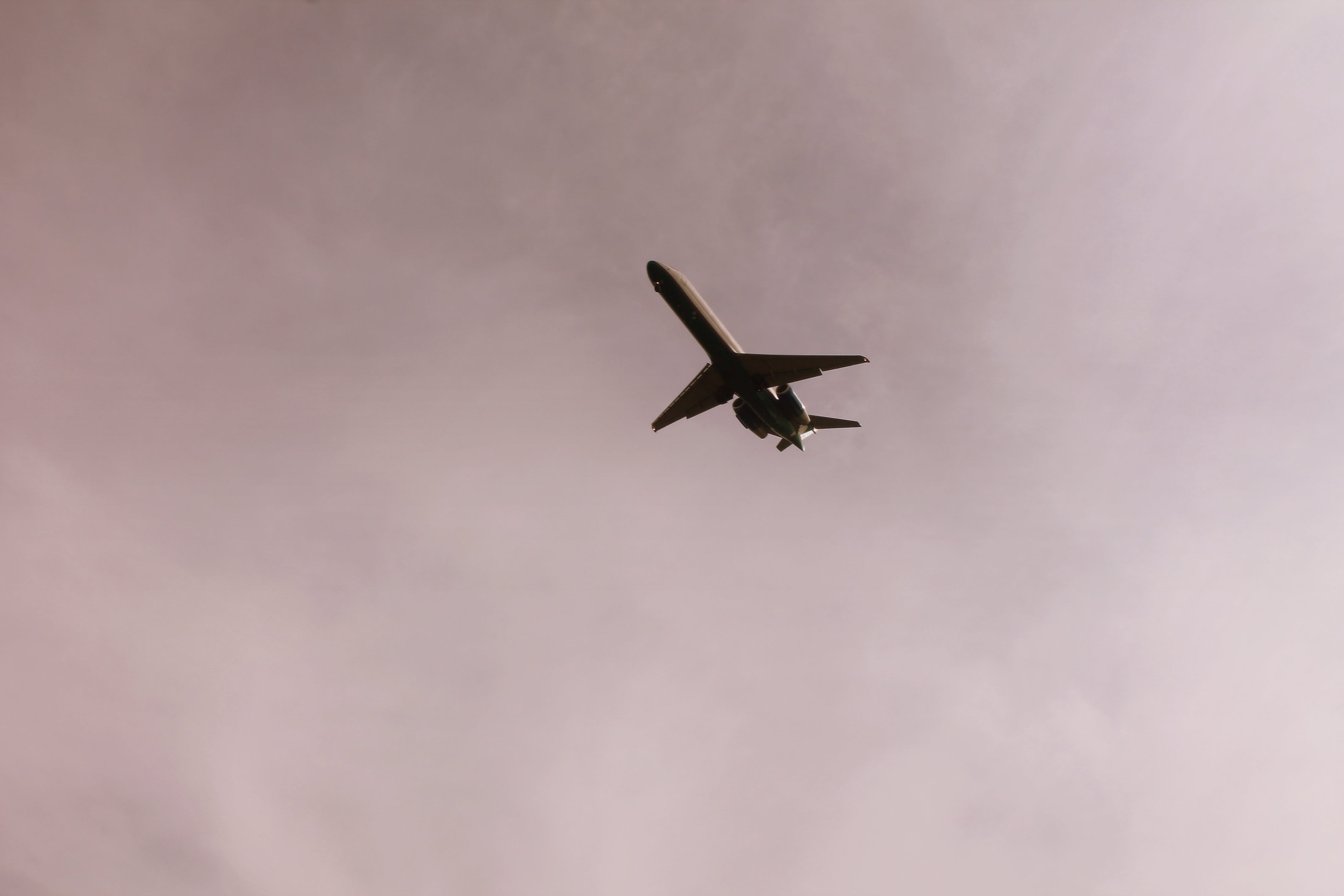Airplane Flying in Mid Air Under Gray Clouds