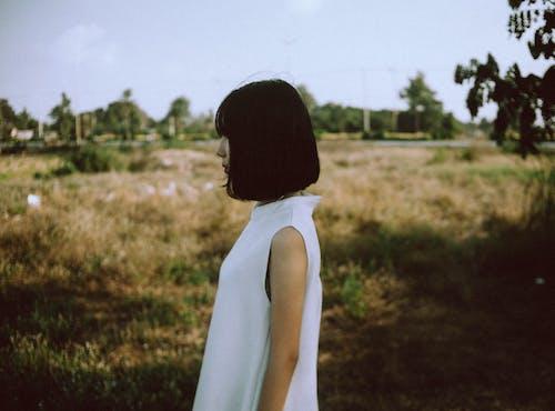 Woman Wearing White Sleeveless Dress Near Brown Grass Field