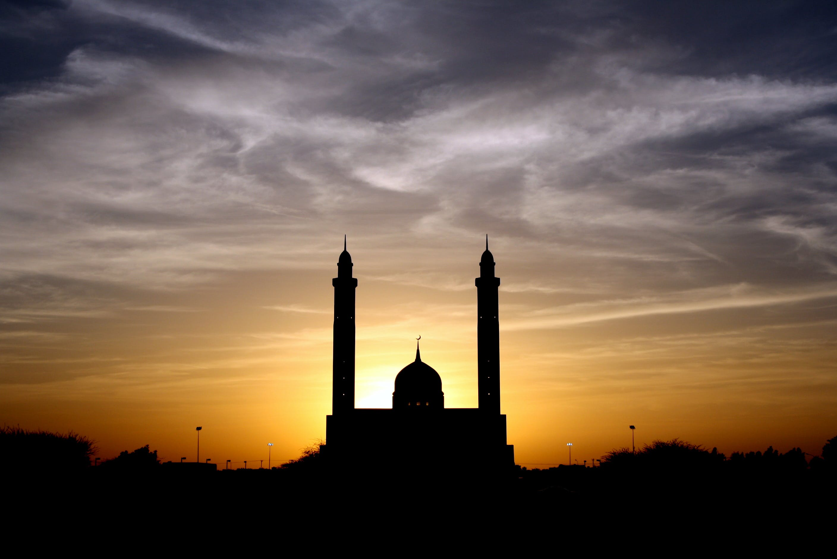 Silhouette of Mosque Below Cloudy Sky during Daytime