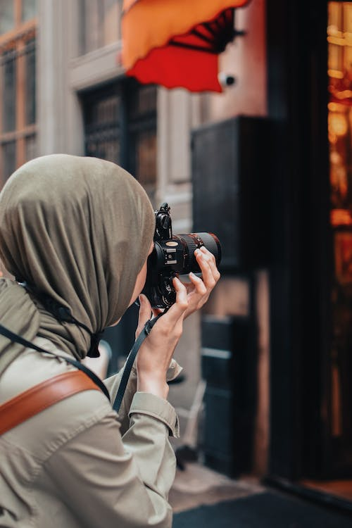 Person in Brown Hoodie Holding Black Dslr Camera