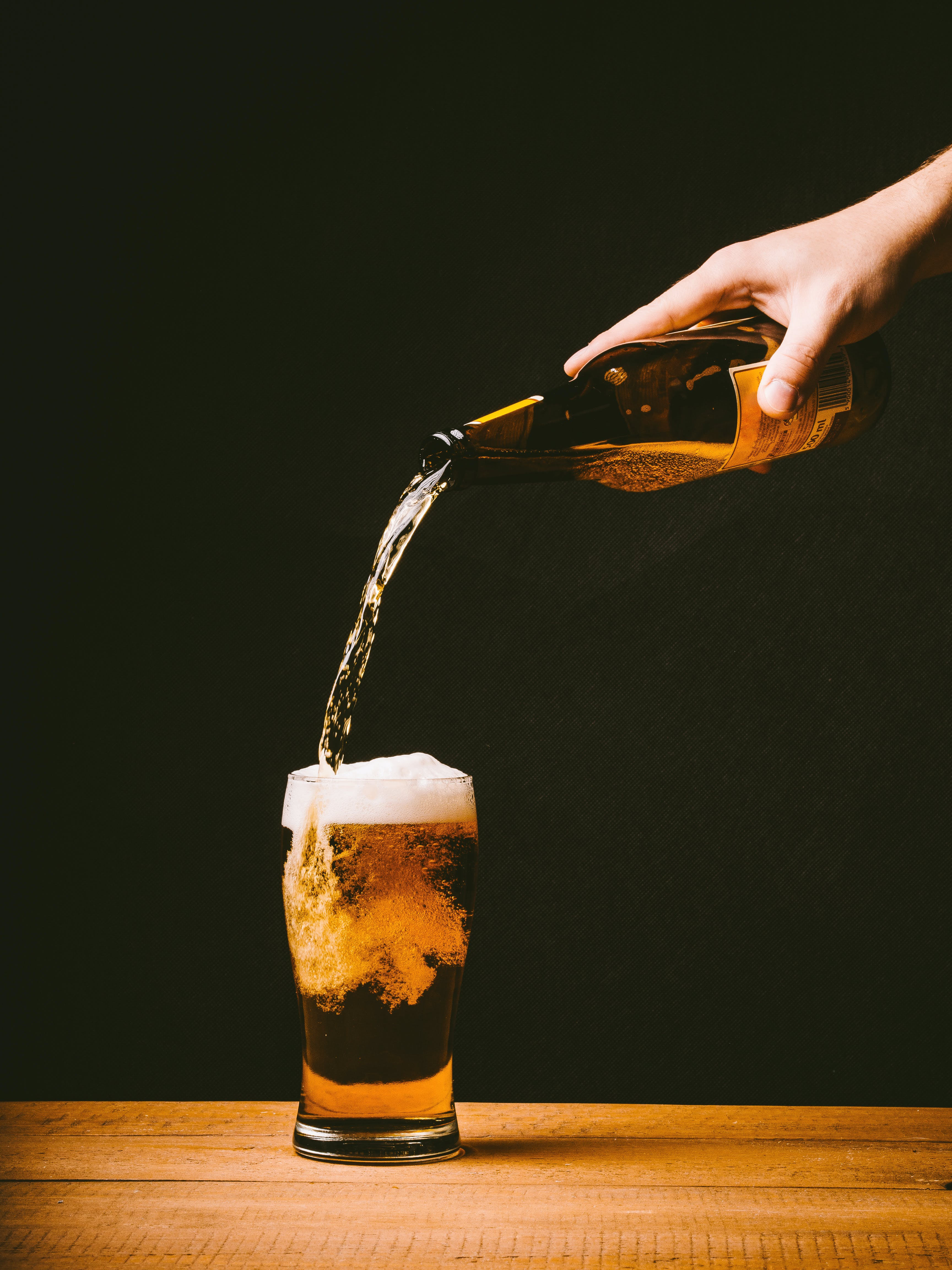 Person Pouring Yellow Liquid on Pilsner Glass Placed on Table