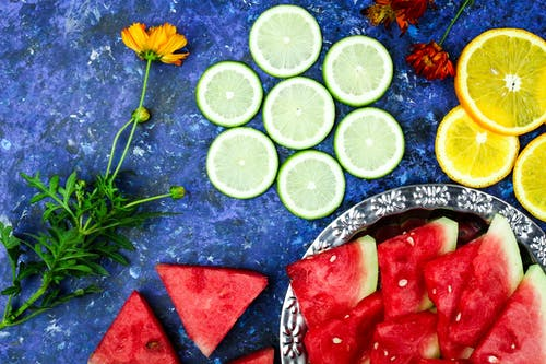 Sliced Fruits Over a Blue Surface