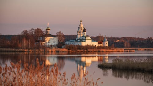 Scenery view of church with domes and withered trees located on shore of calm lake against cloudless sky in sunset