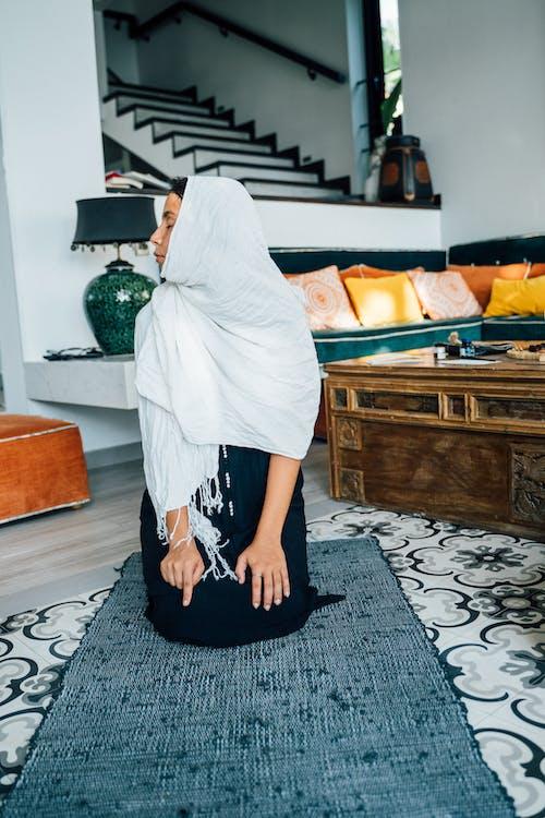 Woman Praying on a Prayer Rug at Home