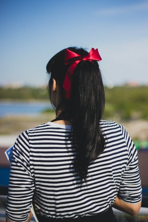 Woman in Black and White Striped Shirt With Red Ribbon in Her Hair