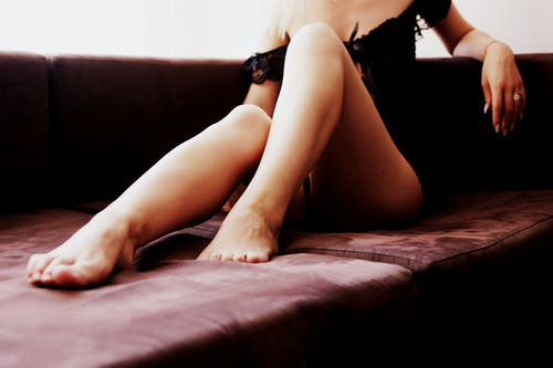 Woman in Black Lace Lingerie Sitting on Brown Bed