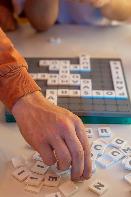 Person Playing Scrabble on White Table