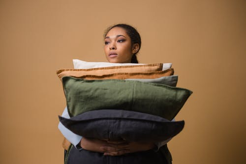Woman Holding A Stack of Throw Pillows