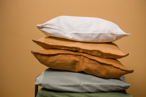 Stack of different colorful pillows folded and placed in stack on chair isolated on dark beige background