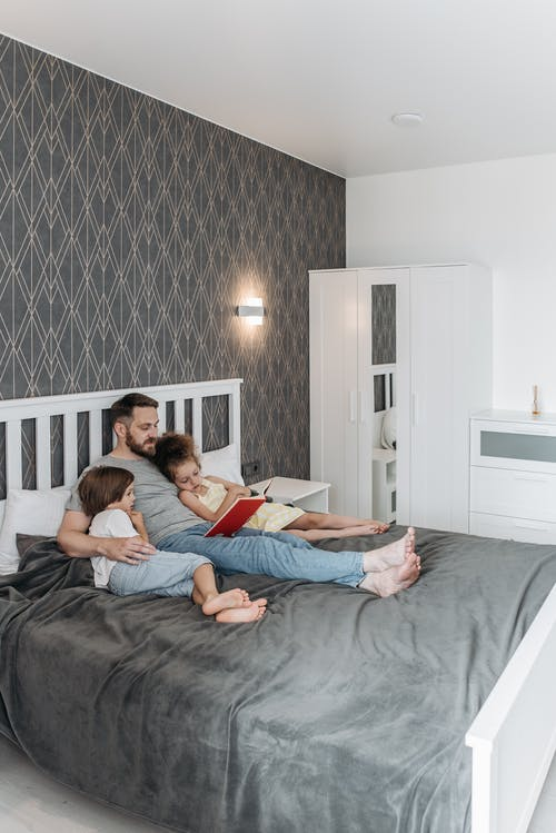 Man and his Children Lying on the Bed