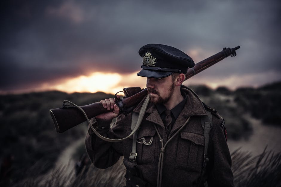 Close-Up Photography of a Man Holding Rifle