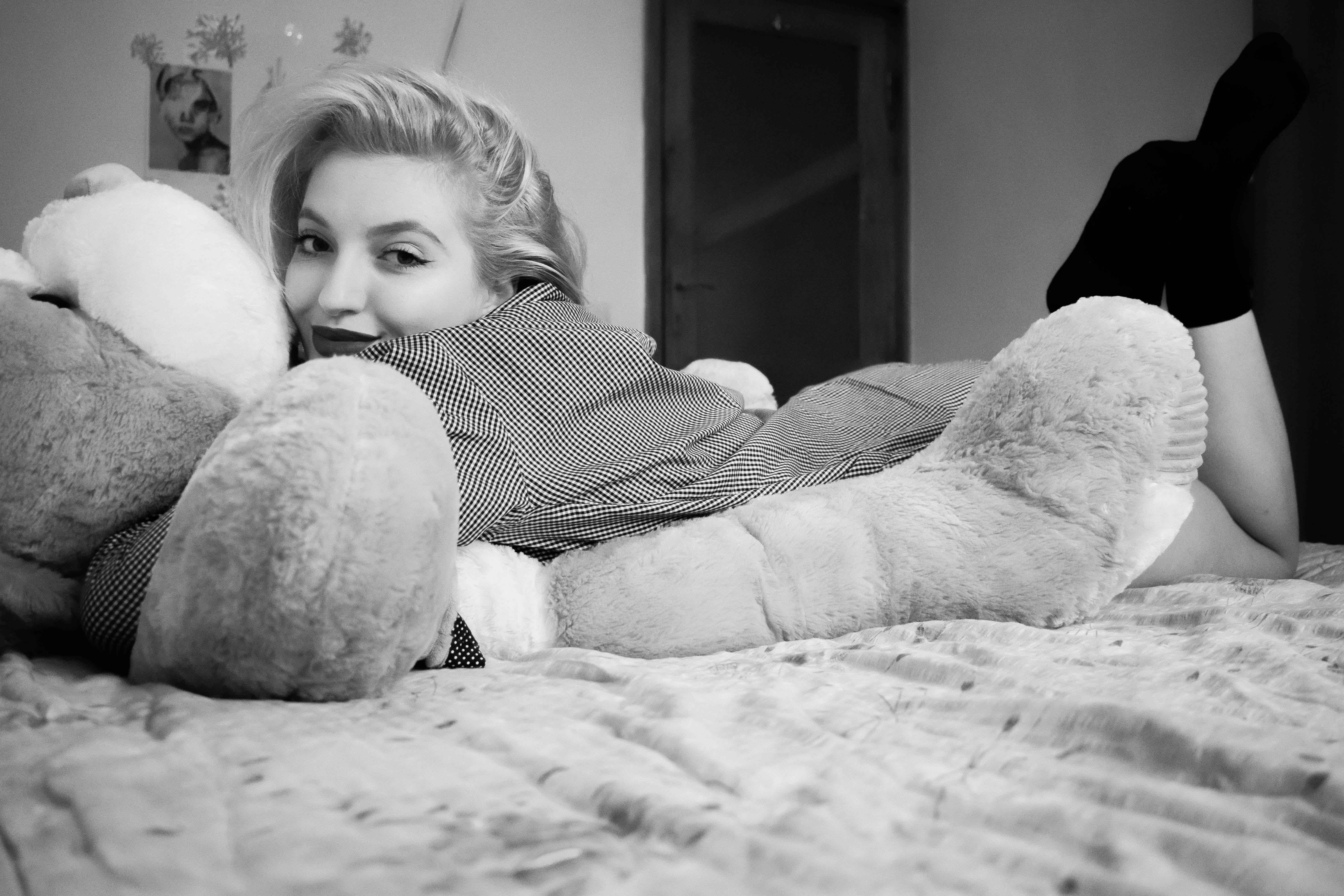 Woman Hugging Bear Lying on Bed