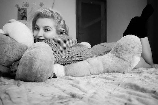 Woman Hugging Bear Lying on Bed