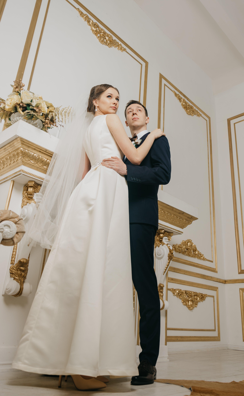 Woman Wearing White Sleeveless Bridal Gown Holding Man